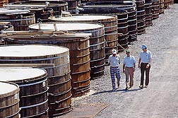 "In 1986, ARS's Henry Fleming (right), best known for helping find the cause of ""bloating� during cucumber fermentation, walks among wooden open-top tanks used by the pickle industry with North Carolina State University professor Ervin Humphries (left) and Douglas Brock of the Mt. Olive Pickle Company."