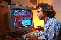Computer specialist analyzes an aerial color-infrared digital video image. Click here for full photo caption.