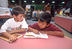 Two Navajo children reading in library: Click here for full photo caption.