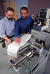 Microbiologists check results of gas chromatographic/mass spectrometric analysis of gaseous compounds from soil. Click here for full photo caption.