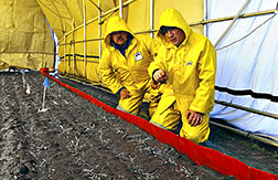 Agricultural engineer Wilkins (left) and technician Goller look for water leaks along a test plot under a rainfall simulator.