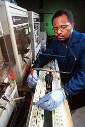 Chemist James Hill places water in an autosampler of the flow-through colorimetric autoanalyzer. Click here for full photo caption.