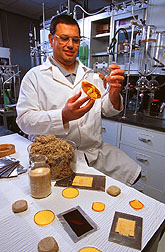 Chemist Navzer Sachinvala demonstrates some of the raw materials and the sucrose-based epoxies used. Click here for full photo caption.