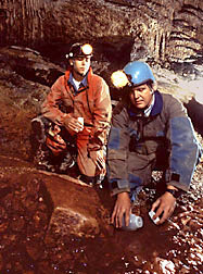 ARS hydrologist Doug Boyer (right) collects water from a stream in a limestone cave.
