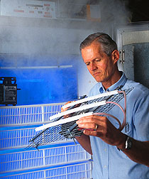 Agricultural engineer Bailey Mitchell demonstrates an electrostatic air cleaning system. Link to photo information.