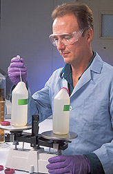 Chemist prepares to use a centrifuge to harvest cyanobacteria and algae: Click here for full photo caption.