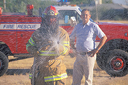 Northwest Fire District Captain uses water and chemical wetting agent to subdue Africanized honey bees while entomologist looks on: Click here for full photo caption.