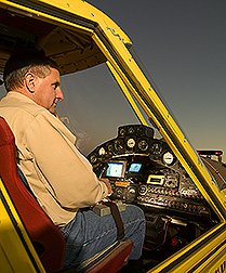 Pilot activates cameras located in agricultural aircraft with a remote control strapped to his leg: Click here for full photo caption.