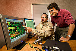 Technician and agricultural engineer compare infrared image to a standard photo: Click here for full photo caption.