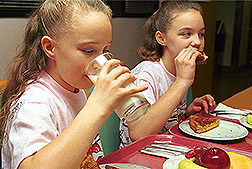 Two girls sitting at a table where one is drinking milk and the other is eating: Click here for full photo caption.