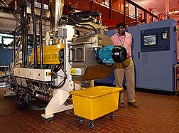 Charles Onwulata stands beside machinery that is part of the pilot plant. Link to photo information