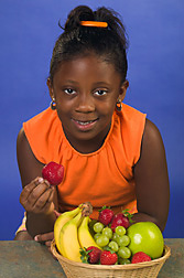 Girl about to eat a strawberry that she picked from a bowl of fresh fruit. Link to photo information