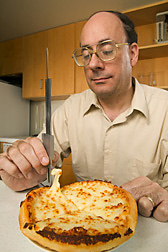 Chemist measures the stretchability of low-fat mozzarella cheese on a commercial take-out pizza: Click here for full photo caption.