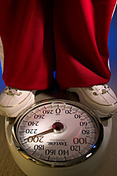 Closeup of a weight scale that tops 200 pounds, along with the feet of the person standing on it. Link to photo information