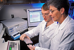 Chemist and physiologist examine a tray of serum samples: Click here for full photo caption.
