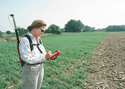 Natural Resources Conservation Service hydrologist uses a global positioning system in Iowa to record the status of a filter strip planting: Click here for full photo caption.