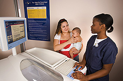 At the ARS Children's Nutrition Research Center at Baylor College of Medicine in Houston, Texas, a mom volunteers her infant for body fat measurement: Click here for photo caption.