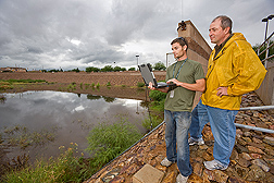 Technician Jim Riley (left) and hydraulic engineer Dave Goodrich download water-level data from the Rostrin Basin, a flood detention pond in Sierra Vista, Arizona: Click here for full photo caption.