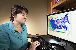 Plant geneticist Stephanie Greene examines a digital map of absolute minimal temperature: Click here for full photo caption.