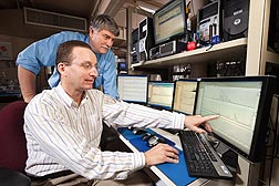 "Chemists Craig Byrdwell (foreground) and James Harnly, with the Beltsville Human Nutrition Research Center, review data from one of the liquid chromatography/mass spectrometry machines used in a process called ""triple-parallel mass spectrometry."": Click here for full photo caption."