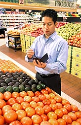 Photo: Man in a grocery store produce aisle checking information on a hand held device. Link to photo information