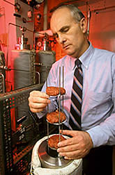 Chemist Jerry King inserts ground beef patties into a high-pressure extraction vessel. Click here for full photo caption.