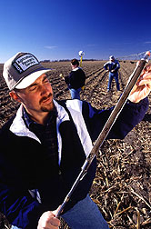 An ARS physical scientist checks a soil sample while an ARS soil scientist withdraws another. Click here for full photo caption.