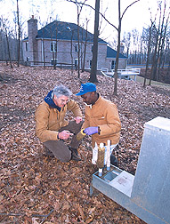Photo: Scientists check a four-poster feeder  in a Maryland suburb. ARS tick-control efforts are targeting the female blacklegged tick. Link to photo information