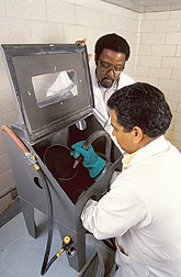 Photo: Chemist Charles James (left) and food technologist Harmeet Guraya conduct a flourblasting test on long-grain brown rice.