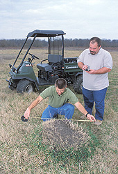 Technician measures a black imported fire ant mound while an entomologist records data: Click here for full photo caption.