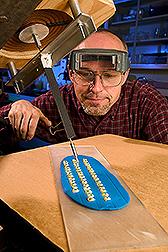El técnico John Abt inyecta virus en las semillas de maíz que están germinando usando el método de inoculación por perforación vascular. Enlace a la información en inglés sobre la foto