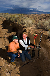 Near a potato field, Jorge Delgado and Alan Stuebe kneel to study a 4-foot-deep area of soil exposed by a trench. Link to photo information