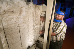 A machinist replaces a broken bale tie on a cotton bale: Click here for full photo caption.