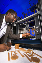 Charles Onwulata inspects molded dairy bioplastic made from surplus whey proteins. Link to photo information