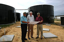 Soil scientists and CEO of Super Soil Systems discuss construction drawings of a lower cost version of the manure treatment system (background) used on a 6,000-head swine farm in North Carolina: Click here for full photo caption.