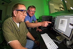 Chemist (left) and veterinary medical officer discuss a Western blot image from a TSE test of formalin-fixed tissues: Click here for full photo caption.