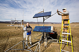Plant physiologist (left) and technician check sensors and download carbon dioxide flux data from an eddy covariance system on a pasture at Penn State, Haller research farm: Click here for full photo caption.
