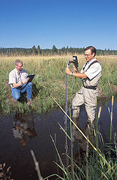Rangeland scientist and wildlife program manager measure streamflow: Click here for full photo caption.