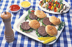 Freshly cooked hamburgers sit on a picnic table.