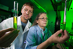 J'Lynn Howell homogenizes hydrilla samples while Franck Dayan observes carotenoids in test tube that indicate a plant is herbicide resistant. Link to photo information