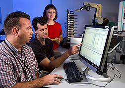 U.S. Army Medical Research Institute of Infectious Diseases microbiologist (left) and two ARS plant pathologists (center) use the novel robotic diagnostic technology known as TIGER to diagnose plant diseases: Click here for full photo caption.
