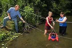 ARS soil scientist, University of Maryland support scientist (center), and ARS chemist use an Acoustic Doppler Channel Profiler to assess water velocity and channel geometry of a Choptank Watershed stream: Click here for full photo caption.