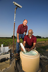 University of Maryland associate professor (kneeling) and ARS soil scientist collect water quality samples from an automated sampler: Click here for full photo caption.