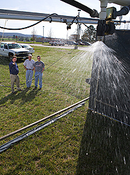 ARS and University of Arkansas scientists conduct a rainfall simulation to determine the long-term effect of alum-treated poultry litter on aluminum and phosphorus runoff: Click here for full photo caption.