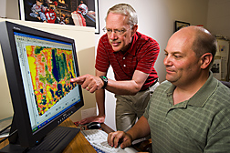 Two agricultural engineers evaluate a soil electrical conductivity map to estimate field nutrient levels and salinity in a vegetative treatment area: Click here for full photo caption.