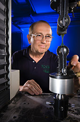 Using an Instron universal testing machine, a technician evaluates the mechanical properties of a tensile bar from chemically modified zein: Click here for full photo caption.