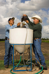 Technician (left) and welder prepare compost tea by pouring compost into an extractor: Click here for full photo caption.