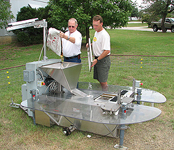 Entomologist (left) and technician load corn, used as bait to attract deer, into the hopper of an automatic deer-collaring device: Click here for full photo caption.