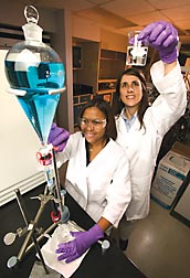A column filled with poultry litter-based activated chars is put to the test by chemist Isabel Lima (right) and Bonnie Dillon by letting a solution of copper ion pass through: Click here for full photo caption.
