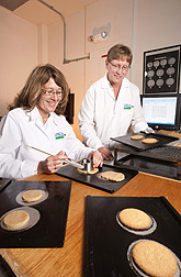 Research assistant Sharon Croskey (left) of Ohio State University cuts whole-grain wheat flour cookie dough for baking-quality tests as ARS technician Amy Bugaj sets baked cookies on a cooling rack: Click here for photo caption.